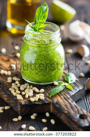 Basil pesto sauce with ingredients: fresh green basil, pine nuts and garlic  on the wooden rustic background - stock photo