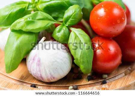 Basil, tomato, garlic and corn pepper on wooden cutting board - stock photo