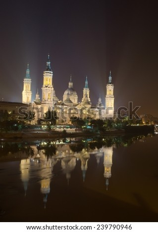 basilica del pilar in spanish zaragoza is illuminated during night and it is being reflected on surface of river ebro.