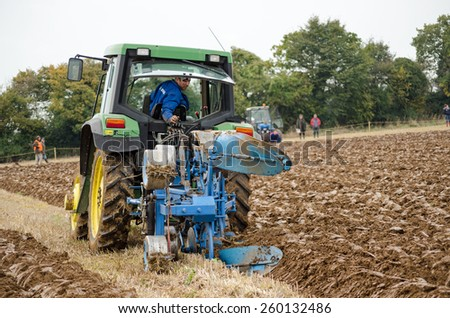 BASINGSTOKE, UK  OCTOBER 12, 2014: A competitor on a modern tractor taking part  in the British National Ploughing Championships.  Competing in the one way ploughing  reversible class. - stock photo