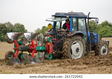 BASINGSTOKE, UK  OCTOBER 12, 2014: Peter Alderslade on Valtra tractor in the British National Ploughing Championships.  Alderslade won the one way ploughing  reversible class. Accredited photographer - stock photo