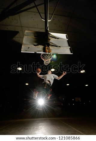 Basket and basektball player jumping with ball and aiming at basket with lights turned on at night - stock photo