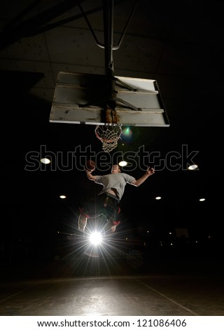 Basket and basektball player jumping with ball and aiming at basket with liights turned on at night - stock photo