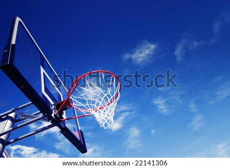 Basket ball net and rim set against blue sky and white fluffy clouds - stock photo