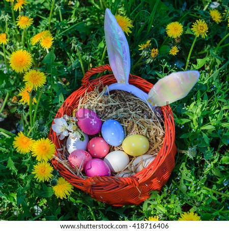 Basket Easter eggs in blossoming dandelion on spring day - stock photo