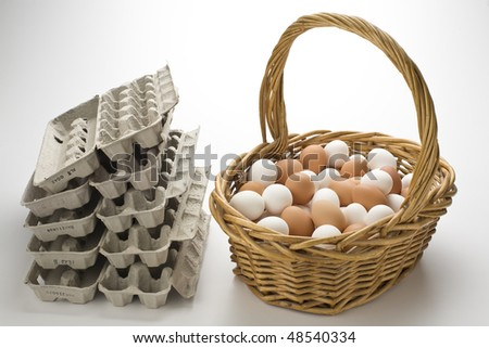 Basket filled with brown and white eggs with empty  egg cartons - stock photo