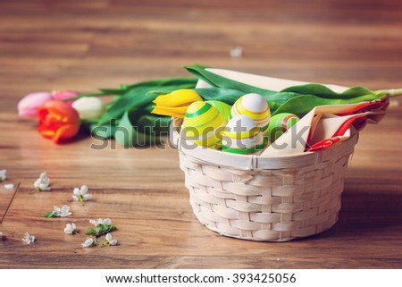 Basket full of easter egg decorations with floral arrangement - stock photo