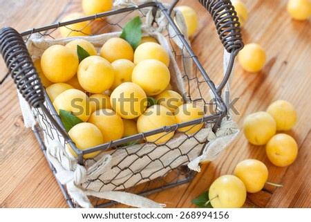 basket full of ripe yellow plums - stock photo