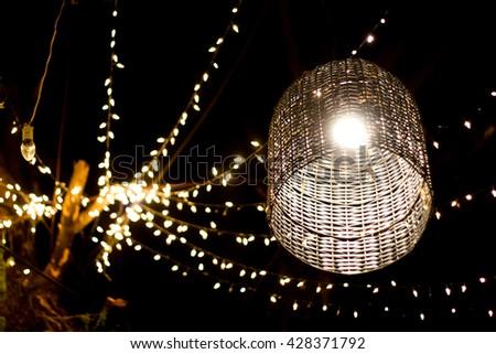 basket lamp decoration garden on tree at night time - stock photo