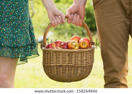 Basket of apples being carried by a young couple outside on sunny day - stock photo