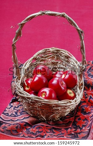 Basket of apples on red background - stock photo