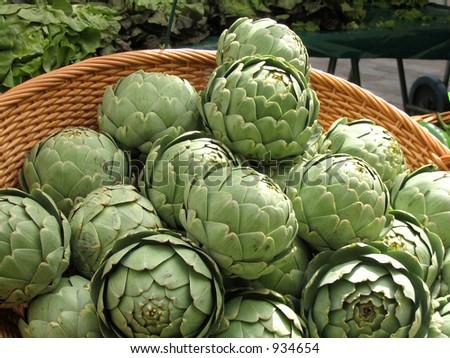 Basket of artichokes in outdoor market in Paris - stock photo
