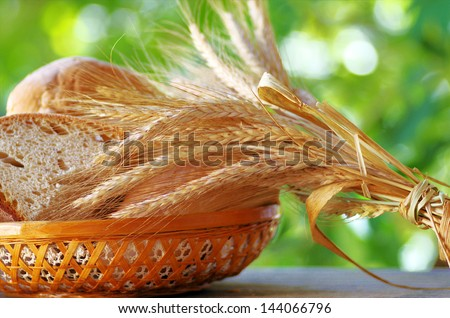 Basket of  bread , wheat spikes on table . - stock photo