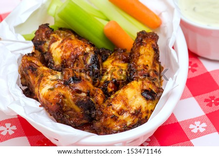 Basket of chicken wings with dip, celery & carrots - stock photo