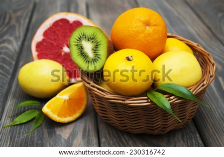 Basket  of Citrus Fruits on a wooden background - stock photo