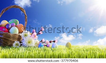 Basket of Decorated Eggs With Flowers On Green Meadow - Easter Holiday Background  - stock photo