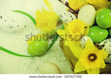 Basket of easter eggs with flowers - stock photo