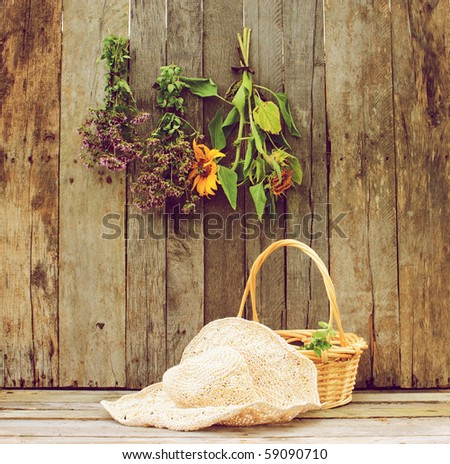 Basket of fresh cut oregano, a gardener's straw hat and herbs and sunflowers hung to dry on a rustic barn background. - stock photo