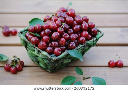 Basket of fresh ripe cherries on the wooden table - stock photo