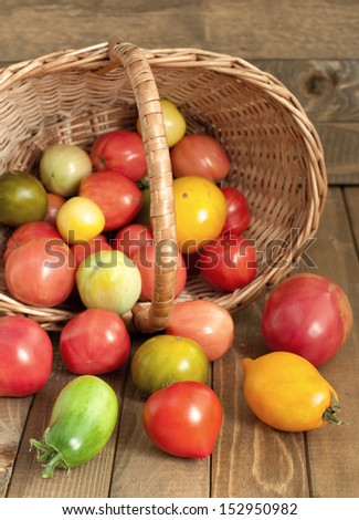 Basket of fresh tomatoes on wooden table, rustic style, vertical