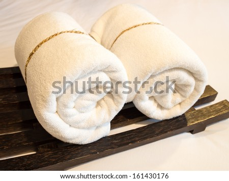 Basket of pure white towels in bedroom - stock photo