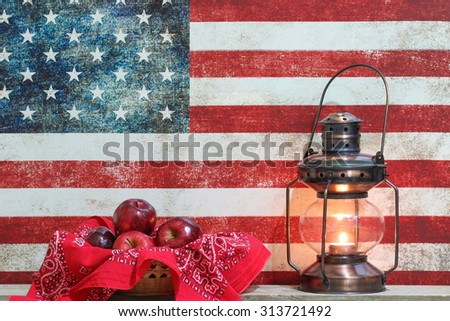 Basket of red apples and antique lantern by vintage American flag canvas background - stock photo