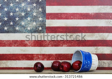 Basket of red apples by vintage American flag canvas background - stock photo