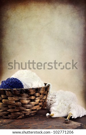 Basket of soft balls of yarn with needlework and knitting needles lying nearby. Room for copy space. - stock photo