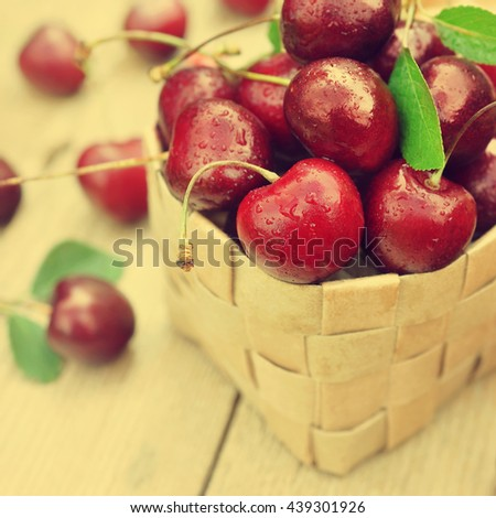Basket of sweet  fresh cherries on green grass background, selective focus, toned
