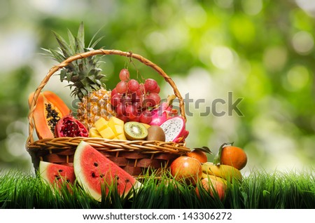 Basket of tropical fruits on green grass.
