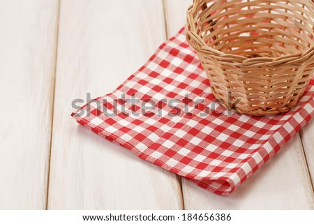 Basket on picnic table/Basket on wooden table. Red plaid cloth - stock photo