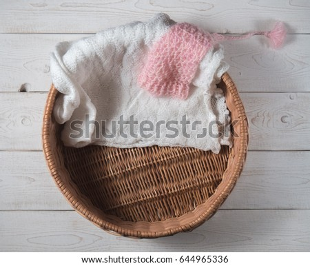 basket, pink hood and knitted blanket for a newborn photo shoot