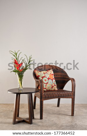 Basket weaved seater chair with flower in a vase - stock photo