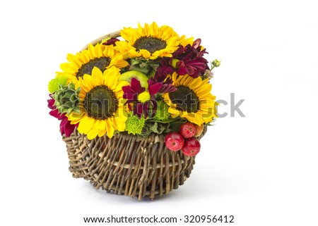 basket with autumnal flowers, berries and apples on white background - stock photo