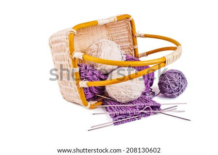 Basket with balls of wool yarn and knitting needles isolated on a white background - stock photo