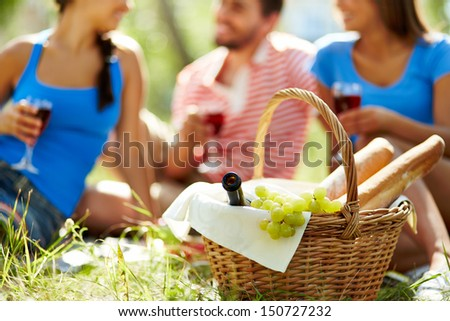 Basket with bottle, grapes and baguettes on background of group of friends - stock photo