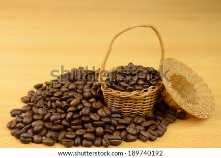 Basket with coffee beans, a handful of near spilled coffee on the table - stock photo