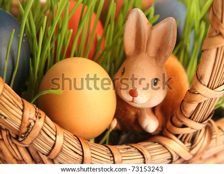 basket with colored eggs on white - stock photo