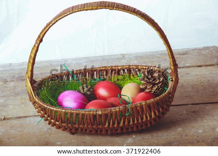 Basket with colorful eggs on the table Easter - stock photo