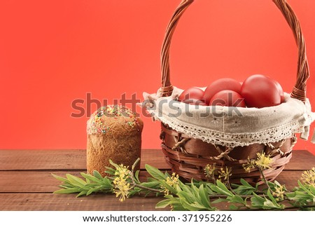 Basket with easter cake and red eggs on rustic wooden table - stock photo