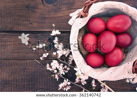 Basket with easter cake and red eggs on rustic wooden table. Top view. - stock photo