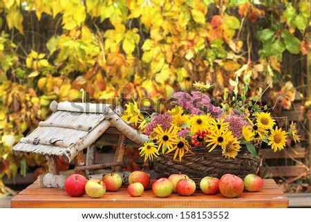 Basket with flowers and  red apples in autumn outdoors - stock photo