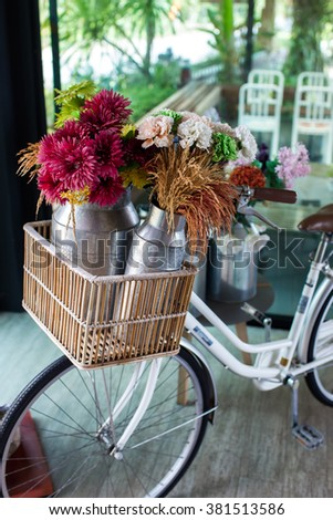 Basket with flowers on vintage city bicycle - stock photo