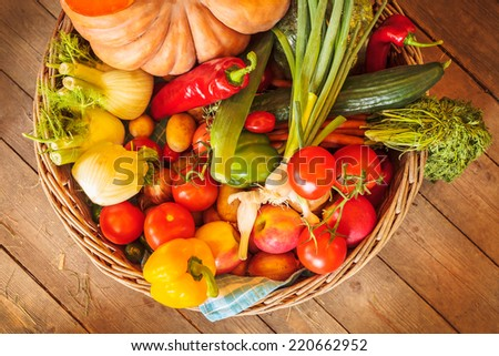 Basket with fresh organic vegetables on an old wooden floor - stock photo