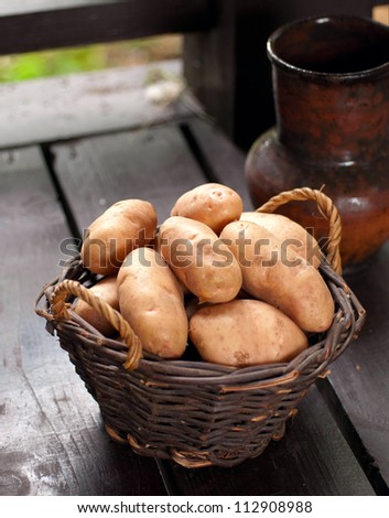 Basket with fresh Potatoes on wooden background