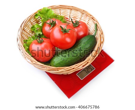 Basket with fresh vegetables on digital kitchen scales, isolated on white - stock photo
