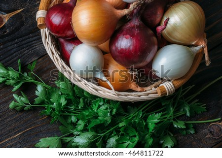 Basket with onions and garlic on a dark background.
