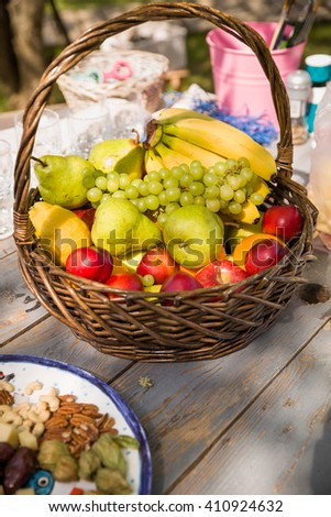 Basket with organic fruit (apples, pears, bananas and grapes) on the wooden table with nuts and other ingredients for outdoor picnic. Healthy food for summer picnic. - stock photo
