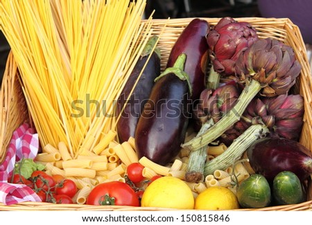 Basket with raw pasta and fresh vegetables, typical italian food - stock photo