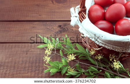 Basket with red easter eggs on rustic wooden table.  - stock photo